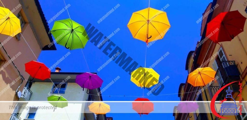 The sky above Monferrato St. full of colored umbrellas